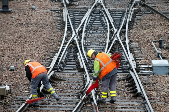 FILE PHOTO: French state-owned railway company SNCF workers inspect the tracks at a SNCF depot station in Charenton-le-Pont near Paris