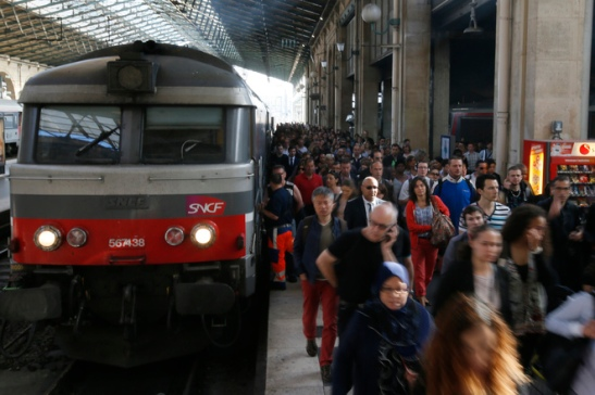 People crowd a platform after a commuter train arrived at the Gare du Nord railway station during a strike by SNCF employees in Paris